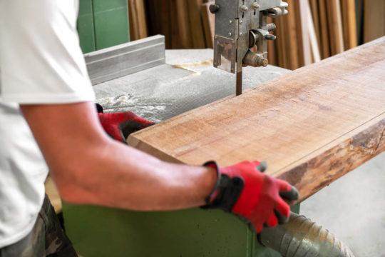 mężczyzna tnie drewno za pomocą piły taśmowej, którą trzeba regenerować